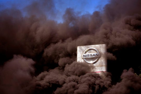 Smoke rises over the Nissan factory as workers burn tires during a protest in Barcelona, Spain, Thursday, May 28, 2020. Japanese carmaker Nissan Motor Co. has decided to close its manufacturing plans in the northeastern Catalonia region, resulting in the loss of some 3,000 direct jobs.