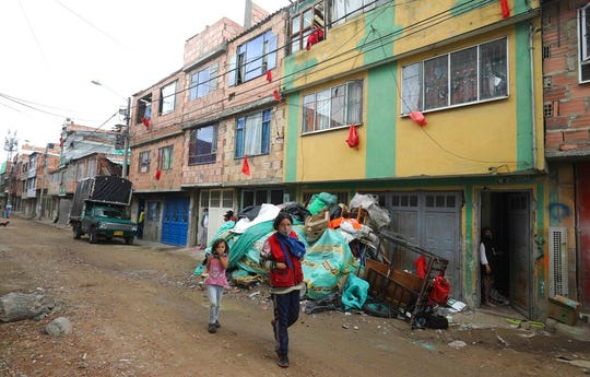Residents in need of food attached pieces of red fabric to their windows to alert the City Hall employees delivering bags of free food to the needy, amid a lockdown to help curb the spread of the new coronavirus, in Bogota, Colombia, Wednesday, May 27, 2020.