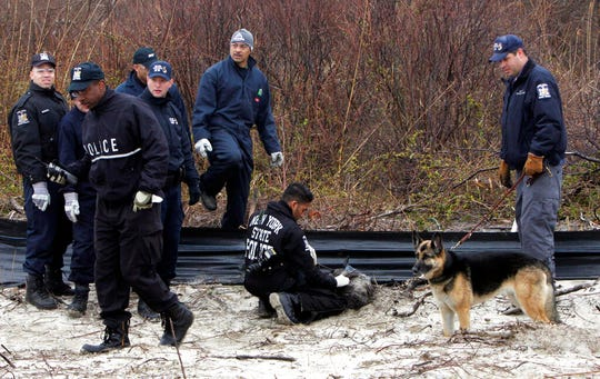 In this April 11, 2011, file photo, law enforcement and emergency personnel examine an object on the side of the road, center, near Jones Beach in Wantagh, N.Y. On Friday, May 22, 2020, authorities investigating the long-running mystery of skeletal remains strewn along a suburban New York beach highway said they have identified the remains of one of the women using DNA technology.