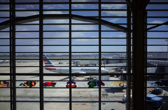 In this file photo taken on March 17, 2020 an American Airlines plane is seen from a terminal of Reagan National Airport in Arlington, Virginia. American Airlines will cut its 17,000 management and support staff by 30%, about 5,100 jobs.