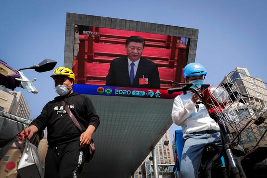 Workers prepare to deliver foods near a TV screen showing Chinese President Xi Jinping attending the closing ceremony of the National People's Congress Thursday, May 28, 2020. China's ceremonial legislature on Thursday endorsed a national security law for Hong Kong that has strained relations with the United States and Britain.