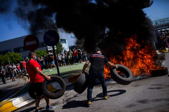 Nissan workers burn tires during a protest in front of the Nissan factory in Barcelona, Spain, Thursday, May 28, 2020.