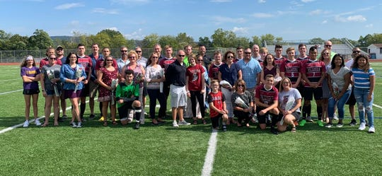 Seniors on the 2019 Elmira High School boys soccer team pose for a photo with family members and head coach Derek Hamilton during Senior Day.