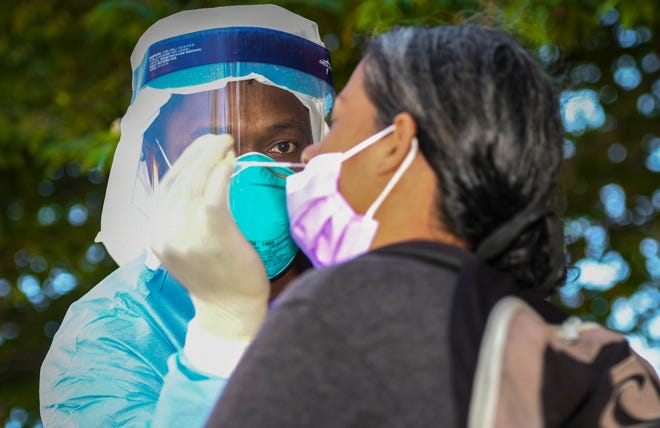 Guam Department of Public Health and Social Services nurse Marc Sexton, extracts a nasal swab sample from a woman who attended a testing session for the coronavirus outside an abandoned parking garage in Tumon on Thursday, May 28, 2020.
