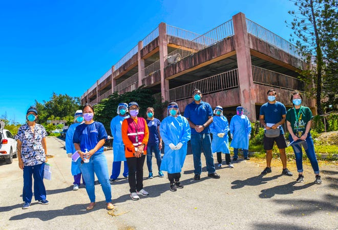 Department of Public Health and Social Services employees and other frontline health professionals gather after a morning of coronavirus testing at an abandoned parking structure, frequented by members of the island's homeless population, in Tumon on Thursday, May 28, 2020.