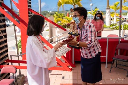 SBCS Principal Sr. Maria Rosario Gaite, RSM hands certificate and award to Valedictorian Amber Pineda.