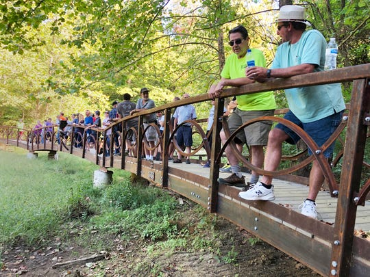 Employees of Henderson-based Pittsburg Tank & Tower Group, spouses and members of the Johnston family gather on the 120-foot-long William Donald Johnston Reflection Bridge beside Wilderness Lake in John James Audubon Park for a dedication ceremony on Sept. 28, 2019.