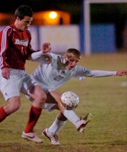 Henderson County's Caleb Mills fights for control of the ball with Daviess County's Ricky Freeman in the 2008 boys regional soccer championship at Apollo.