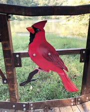 A painted steel cardinal is one of four birds that decorate the William Donald Johnston Reflection Bridge beside Wilderness Lake in Audubon State Park. The others, all painted by wildlife photographer and visual artist Randall Wilkerson, include a bald eagle, mallard duck and screech owl.