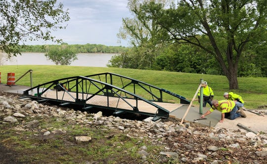 Contractors on May 12 finish the concrete approaches to the bridge on the RiverWalk in Atkinson Park that was fashioned from a portion of a roof truss that was salvaged during the demolition of the former Green's Rollodrome on Watson Lane in the early 1990s.