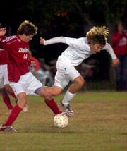 Henderson County's Tyler Book gets tripped as he battles for control of the ball against Daviess County's Davin Shaw in the 3008 boys regional soccer championship at Apollo.