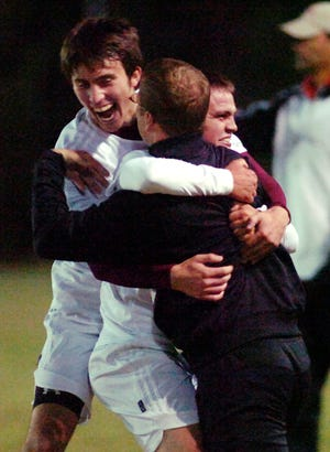 Henderson County's Ryan Lingerfelt, left, and Jordan Gregory share a victory hug with head coach Brian Crafton after defeating Daviess County in the 2008 boys regional soccer championship at Apollo.