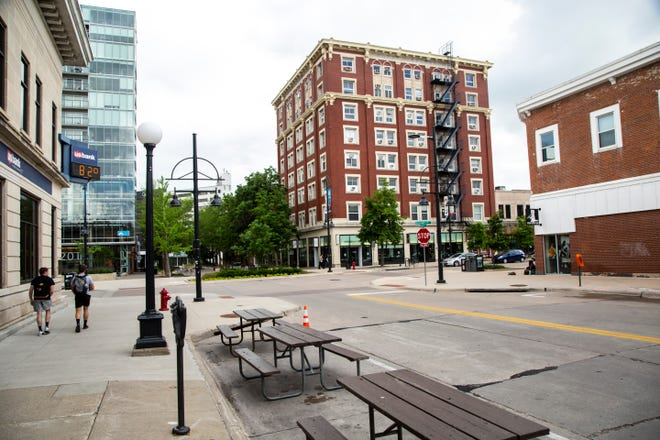 Picnic tables are set out in closed off parking space during the novel coronavirus pandemic, Wednesday, May 27, 2020, along Dubuque Street in Iowa City, Iowa.