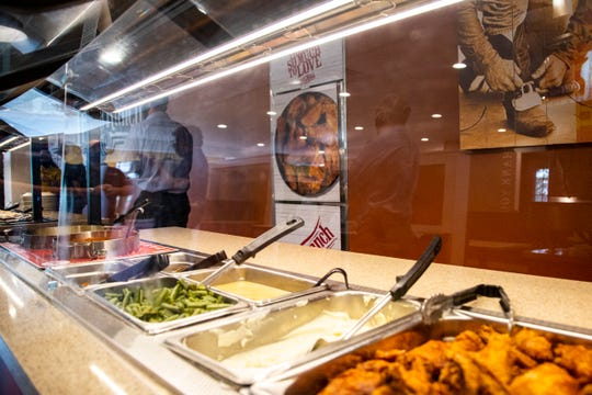 Varieties of buffet items including fried chicken are seen behind a protective plexiglass layer spanning the length of the buffet during a soft opening event, Thursday, May 28, 2020, at Pizza Ranch in North Liberty, Iowa.