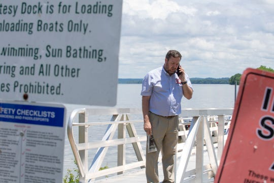 Benton County Mayor Brett Lashlee takes a phone call at Eva Beach Recreational Area in Eva, Tenn., on Thursday, May, 28, 2020. Lashlee waits for bass to be delivered at the Tennessee River.