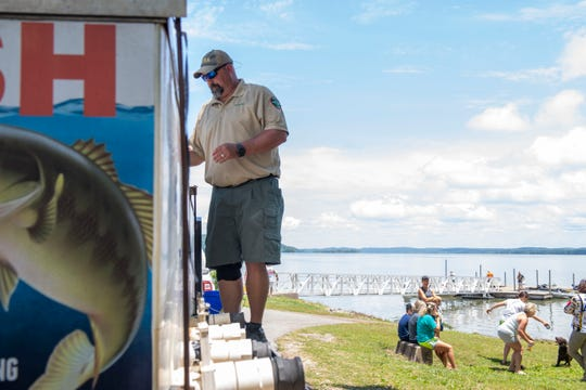 Michael Clark with the Tennessee Wildlife Resources Agency inspects the bass before they are placed in the Tennessee River at Eva Beach Recreational Area.