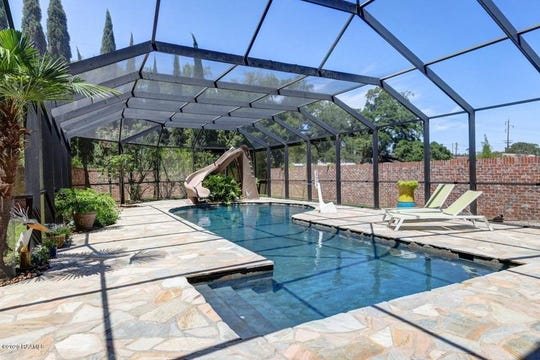 "The pool area has beautiful flagstone pavers, a slide and is enveloped in a spacious screen structure. This mansion in the heart of ""Old Lafayette,"" located at 109 Mossy Oaks, has 5 bedrooms, 4.5 bathrooms in 5,100 square feet, and on the market for $1,450,000."