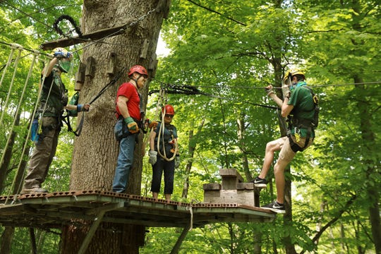 At Hocking Hills Canopy Tours, a masked and shielded Kyle Rowland, left, and Justin Bush, instruct zip liners Jerry and Georgie Hughes on Wednesday about how to safely glide through the Hocking County tourist attraction. Some of the new COVID-19 prevention protocols include smaller groups and employees wearing masks and sometimes shields.