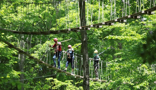 """At Hocking Hills Canopy Tours, a masked and shielded Kyle Rowland, right, leads zip liners Jerry and Georgie Hughes across a sky bridge. Now that it's reopened, the popular tourist spot is seeing plenty of interest. Customers are """"stir crazy, and they're ready to get out,"""" zip line course manager Eric Lapchenko said."""