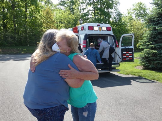 Rita Montgomery, center, hugs her sister after their mom, Maxine Decker, a Heartland of Marion resident, is loaded into a van to be taken to Marion General Hospital on Sunday. Decker has been diagnosed with COVID-19 and was in stable condition on Thursday.