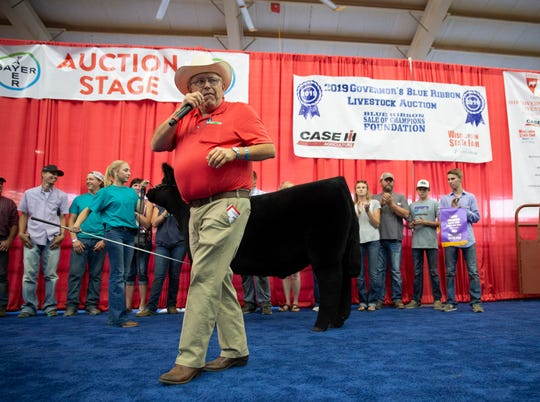 The grand champion steer, a 1,333-pound Maine-Anjou from Burlington is presented by Riley Runkel at the 2019 Wisconsin State Fair Governor's Blue Ribbon Livestock Auction. Runkel's steer was bought for $47,500 by Meijer.