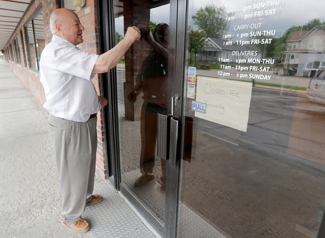 Peter Agnos, the landlord who owns the building that Johnny V's Classic Cafe is in, scrapes the lettering off the door at the closed Johnny V's Classic Cafe in West Allis on Thursday.