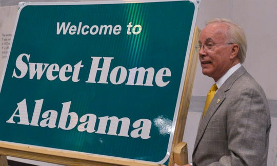 """Lee Sentell, director of the Alabama Tourism Department, with the """"Welcome to Sweet Home Alabama"""" sign."""