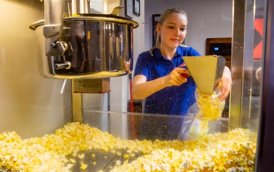 Maia Lewis fills a large bag of popcorn for a customer at Premiere 6 Theatre in Murfreesboro. Before closing its doors due to the pandemic, the theater sold large bags of popcorn so customers could enjoy it at home.