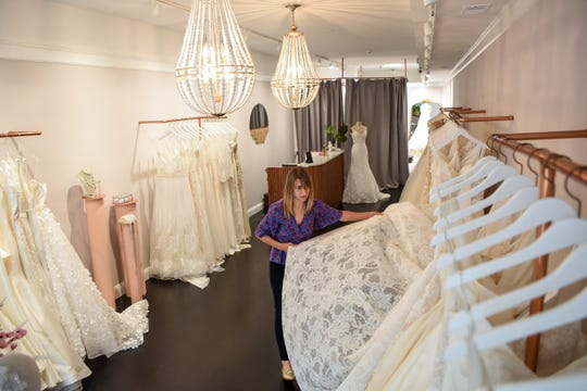 Rachel Sweebe, the owner and stylist of Bridal Atelier in Montclair has had to switch to virtual consultations since the Covid-19 pandemic. Sweebe straightens dresses in the shop on Thursday May 28, 2020.