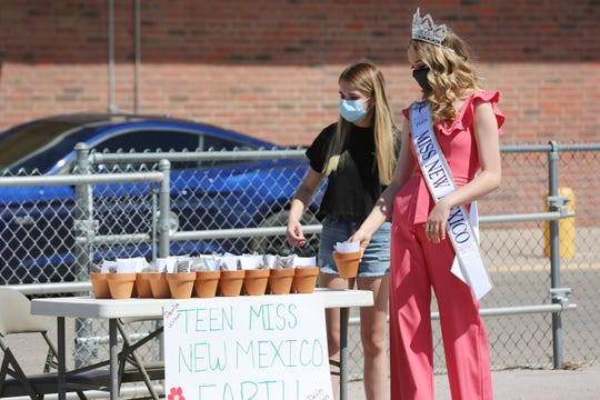 Sisters Lexi (right), and Devin Wilson hand out mini planter kits to kids at Picacho Middle School during school lunch distribution Thursday May 28, 2020.