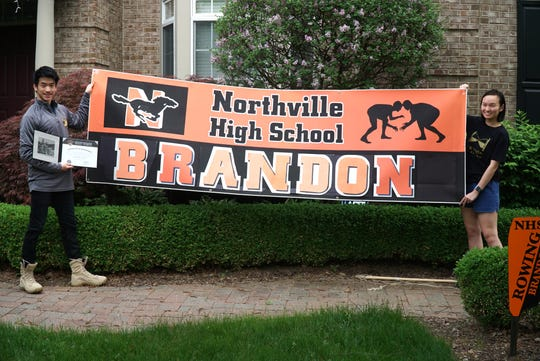 Northville High senior and West Point-bound Brandon Liu gets some help hoisting a sign from his sister Veronica at his home on May 28, 2020.