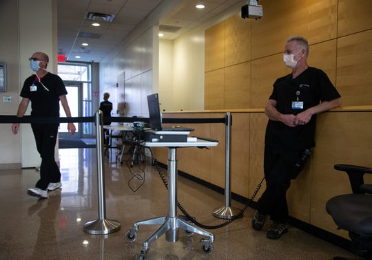 Al Duberchin (right), a medical tech monitors semployees' temperature on May 19, 2020, as they enter the Banner University Medical Center Phoenix.