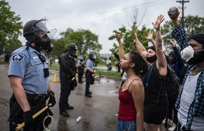 Protesters and police face each other during a rally for George Floyd in Minneapolis on Tuesday, May 26, 2020. Four Minneapolis officers involved in the arrest of the black man who died in police custody were fired Tuesday, hours after a bystander's video showed an officer kneeling on the handcuffed man's neck, even after he pleaded that he could not breathe and stopped moving. (Richard Tsong-Taatarii/Star Tribune via AP)