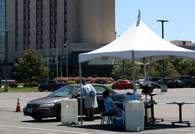 A casino employee gets tested for COVID-19 in the west parking lot of the Atlantis Casino Resort Spa in Reno on May 28, 2020.