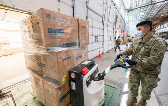 Oregon Army National Guard members load packages of protective masks to be distributed to agricultural workers around the state as part of a collaboration between the Oregon Department of Agriculture and Oregon University Extension.