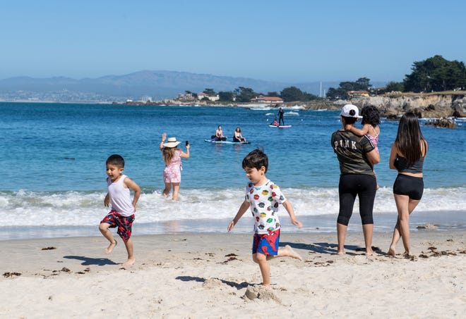 A couple of boys play in the sand at Lovers Point Beach in Pacific Grove, Calif, on Tuesday, May 26, 2020.