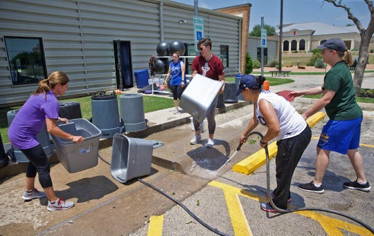 Volunteers and staff with the YMCA in San Angelo help clean up Friday, May 22, 2020 after last week's hail storm caused extensive damage to the facility.