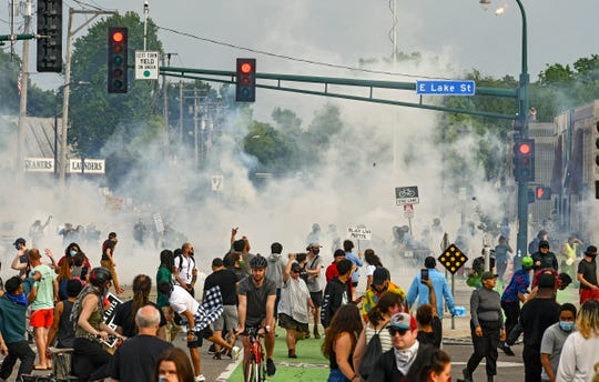 Tear gas floats over protestors in front of the Minneapolis Police Department's Third Precinct headquarters Wednesday, May 27, 2020, in Minneapolis, Minn.