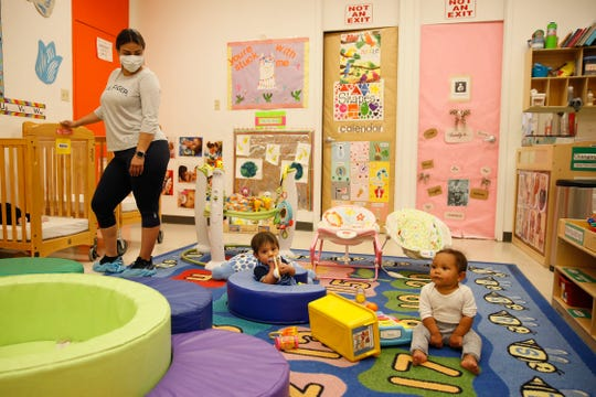 Valerie Velasquez, far left, watches over Izan Rosales and Legacy Wood as they play on the rug during day care Tuesday, May 27, 2020, at the YWCA at the 1600 N. Brown St. location in El Paso.