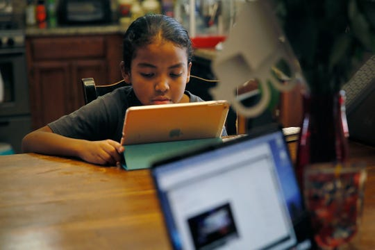 Avery Ray, third grader at Dr. Sue A. Shook Elementary, finishes up their curriculum for the end of the school year Tuesday, May 26, at their home in El Paso.