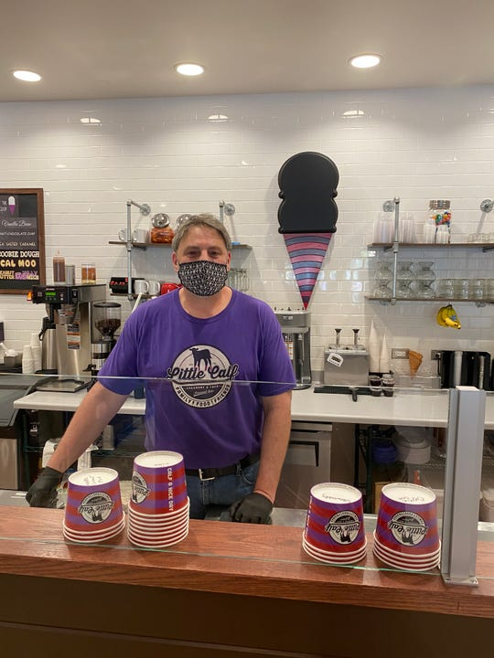 Little Calf Creamery owner Scott Levin poses behind the counter of the business' scoop-shop location on Thousand Oaks Boulevard.
