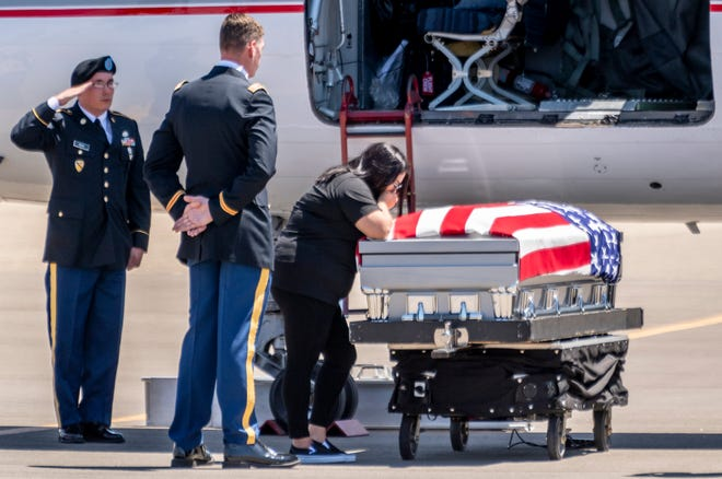 The wife of Army Spc. Juan Covarrubias grieves over his casket on Wednesday, May 27, 2020. Hundreds gathered along roads leading to and at Visalia Municipal Airport on Wednesday, May 27, 2020 to show respect. He was killed March 11 in a rocket attack on Camp Taji in Iraq. His body was taken to Hanford for burial with military honors at the Kings River Cemetery. The COVID-19 pandemic caused delays of return flights for fallen heroes across the country.