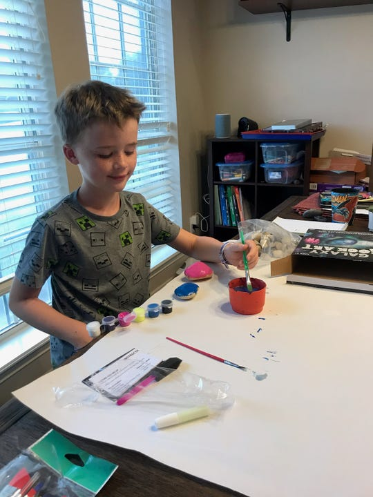Connor Roe, 8, paints some rocks that he and his family plan to hide in local parks. WF Rocks began last year as an online group where people can share their rock creations and finds. The group has now grown to nearly 1,000 members.