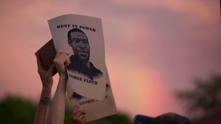 A protester holds a sign with an image of George Floyd during protests on Wednesday night in Minneapolis.