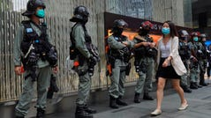 A woman walks in front of riot police in Hong Kong on May 28, 2020.