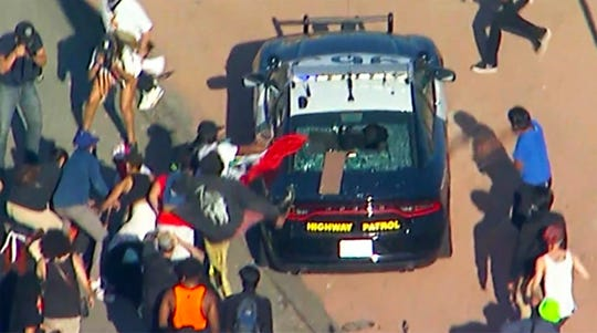 This aerial image provided by KABC-TV shows protesters attacking a California Highway Patrol cruiser during a Black Lives Matter protest on a freeway in downtown Los Angeles on Wednesday.