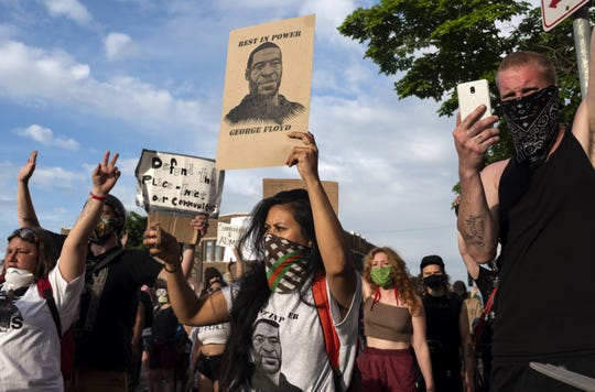 A woman holding a sign and wearing a shirt with George Floyd's face joins other protesters outside the 3rd Police Precinct on May 27, 2020, in Minneapolis, Minnesota. Floyd died in police custody.