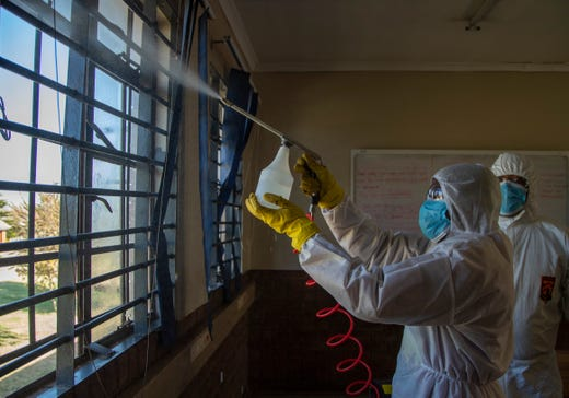 Disinfection team disinfect a classroom at Ivory Park Secondary School east of Johannesburg, South Africa, Thursday, May 28, 2020, ahead of the June 1, 2020, re-opening of Grade 7 and 12 learners to school.