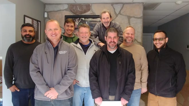 Kostro (second from left) and Lighter (standing in back) are part of the extensive 2-week training course, pictured here with new franchise owners.