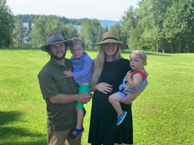Derek Zimmerman holds Rye Zimmerman and Kara Zimmerman holds Sully Zimmerman while standing in front of Pine Cliff Lodge in Ontario. The couple recently began running the lodge, but travel restrictions because of COVID-19 prevent them from returning for much of the summer season.